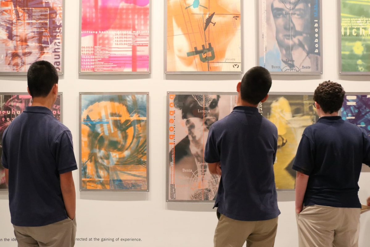 photograph of three youths in navy blue polo shirts looking at posters on a wall
