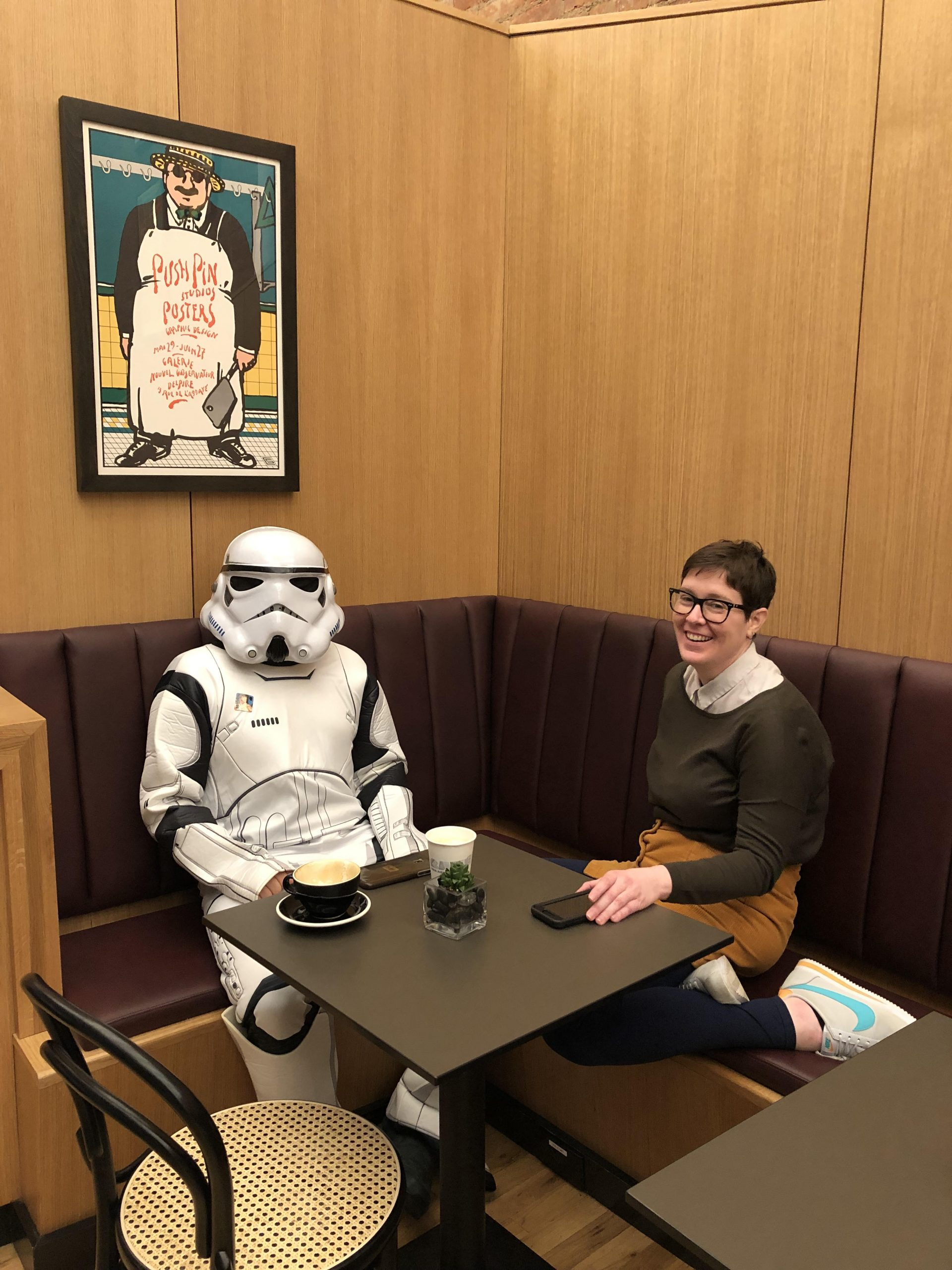 photograph of a woman and a person wearing in a Star Wars stormtrooper costume sitting in a cafe