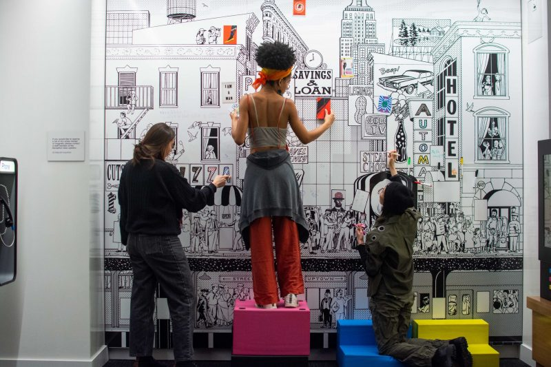 photograph of three woman adding to the 1950's inspired dry-erase board in the Children's Space at Poster House