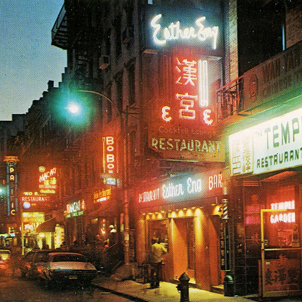 A vintage street photo of chinatown including blinding neon store signage