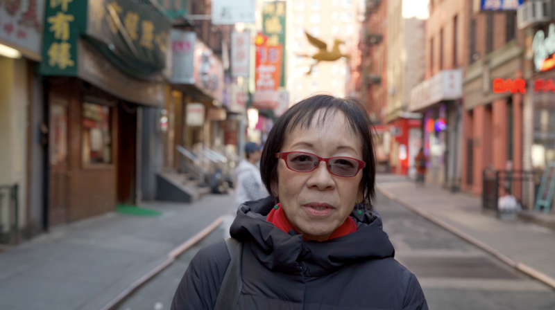 photograph of an asian woman with short hair standing on a Chinatown street