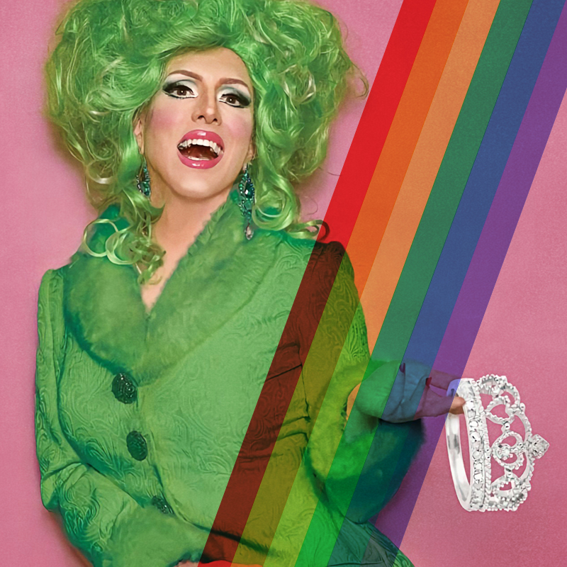 photograph for a Birthday Drag Brunch event of person dressed in green drag holds up a tiara and smiles open-mouthed at the camera