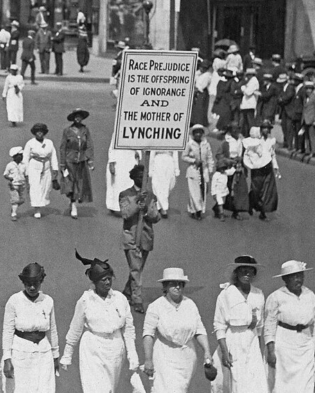photograph of african american marching down fifth avenue holding protest signs