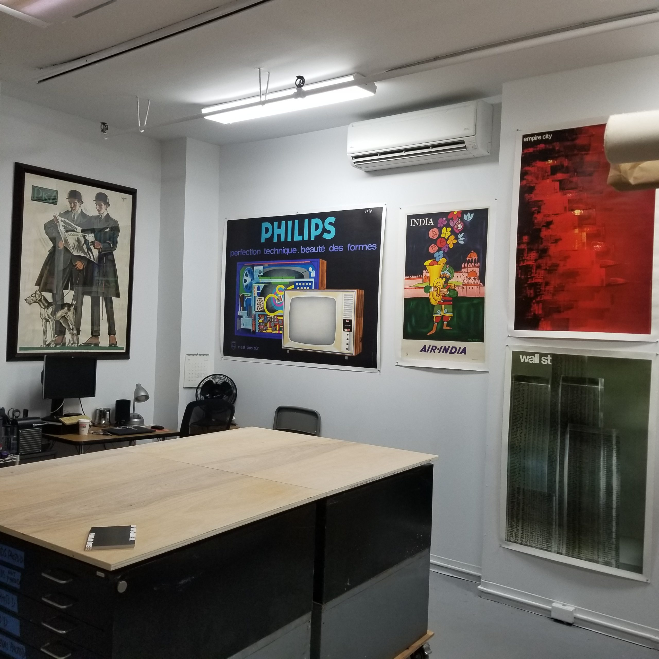 photograph of an interior office space with a large table and posters on the wall