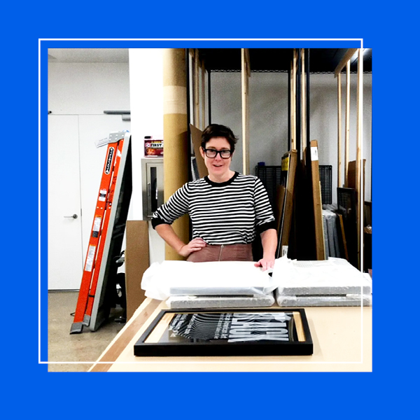 A photo of the archives room in Poster House with the Collections Manager in the center looking at the camera. The photo is framed with a blue frame.