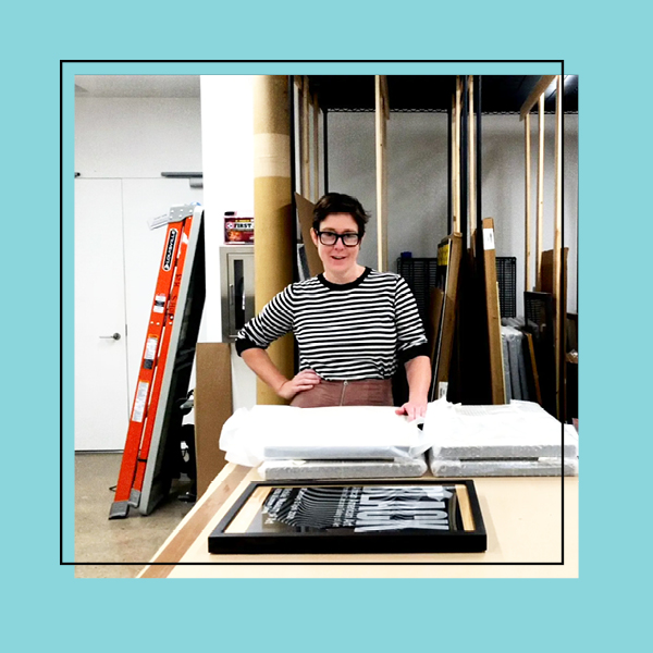 A photo of the archives room in Poster House with the Collections Manager in the center looking at the camera. The photo is framed with a teal frame.