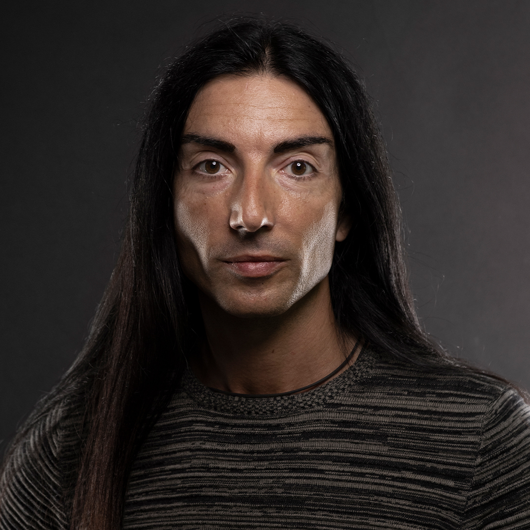 color photo of a man with long black hair staring directly at you
