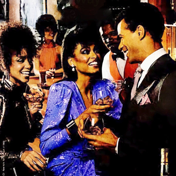 A cropped image featuring two black women and a black man laughing and drinking in a bar.